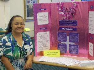 Photo of Executive Director, Roxanne Bolden, sitting in front of an AILH display board.