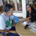 Photo of Lenora and Val Doing Blood Pressure Checks