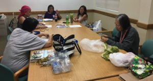 Photo of 5 ladies gathered around a conference table