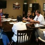 Photo of Kathleen Kenney speaking to the group gathered around a conference table