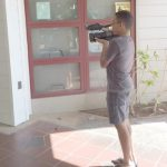 Photo of Ray filming at the doorway of Hale Kuhao