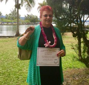 Photo of Sam holding certificate celebrating 6th year anniversary