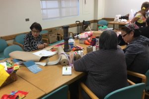 Photo of members of Liv Zentangles sewing around a table