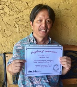 Photo of Thomas Lum holding certificate of appreciation