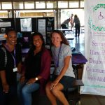 Photo of Julie, Lani, and Kathleen sitting at AILH display table