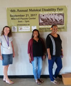Photo of Kathleen, Lani, and Julie standing next to Disability Fair banner