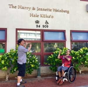 Photo of Thomas and Rene in front of Hale Kuhao sign