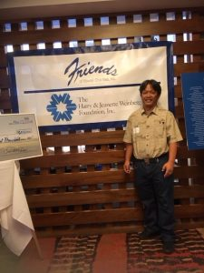 Photo of Thomas Lum standing next to Friends of Hawaii banner