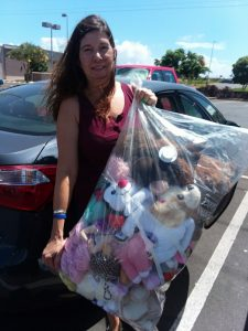Photo of woman holding bag filled with stuffed animals