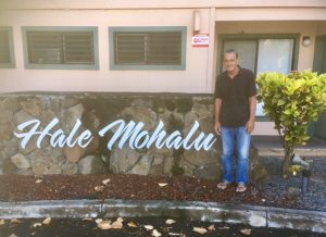 Photo of Anthony Byrd standing next to Hale Mohalu sign