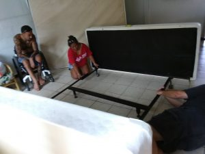 Photo of Lani and Brian setting up bed frame with Victor looking on