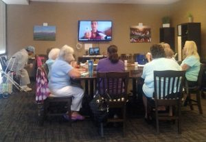 Photo of group sitting around table with large screen TV