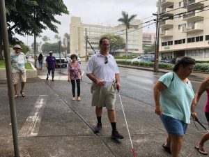 Photo of Brian walking using a white cane