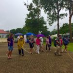 Photo of Kathleen leading participants on white cane walk