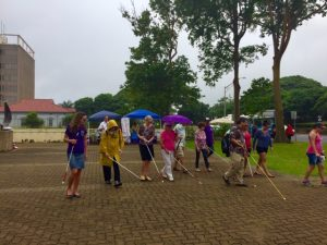 Photo of Kathleen leading participants on white cane walk