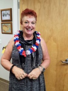 Photo of Sam with red, white, and blue lei