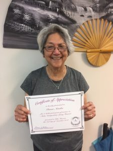 Photo of Pomai holding certificate