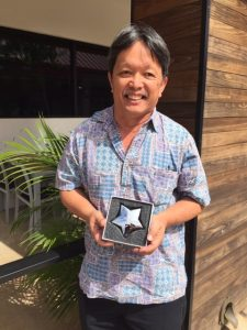 Photo of Thomas Lum holding star shaped award