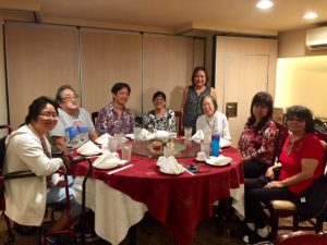 Photo of Hui Malama Po`o sitting around table at holiday luncheon