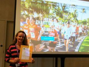 Photo of Kathleen holding packet at Maui Charity Walk Kickoff event