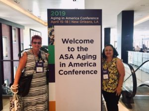 """Photo of Sam and Roxanne standing next to sign that reads """"Welcome tot he ASA Aging in America Conference"""""""