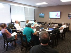 Photo of Maui support group seated around conference table looking at screen