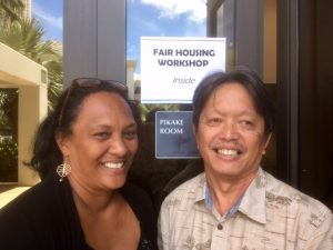 Photo of Julie and Tom in front of sign for Fair Housing Workshop