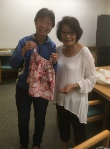 Photo of Florence Tseng and Iris Kaneshiro holding newly finished sewing project